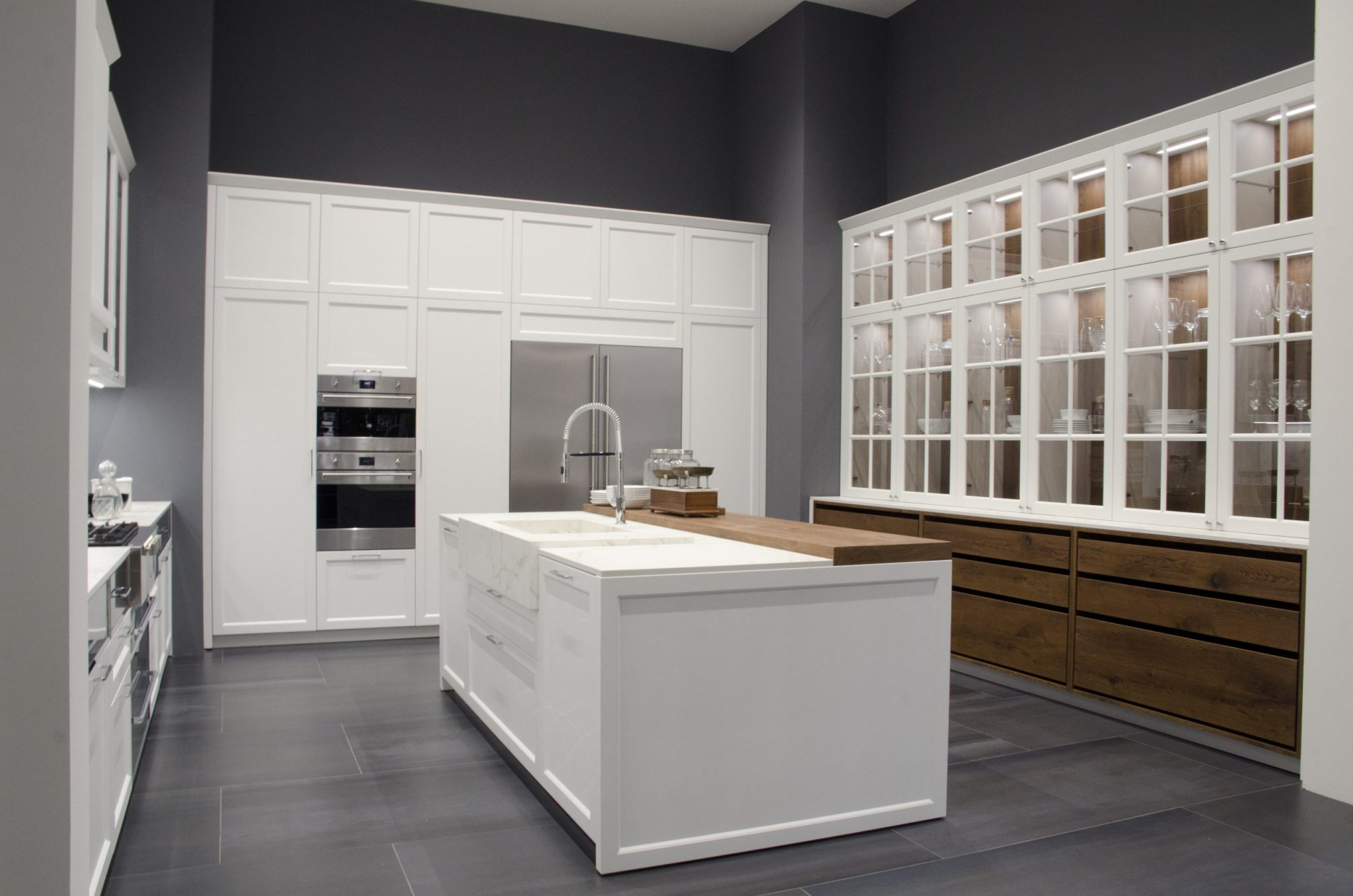 A homage to the traditional kitchen brought up to date with modern touches. The special features: classic framed door, moldings for framing the glass wall units, idea boards, and the touches of warmth from wood and the single-block basins in marble, also used for a sophisticated and practical back for the cooking area.